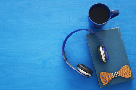 audio book: cup of coffee, old book with headphones on blue wooden background. top view image