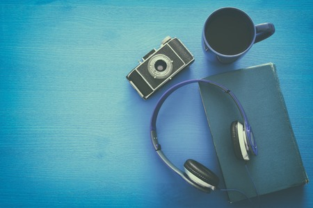 audio book: cup of coffee, old book, vintage photo camera and headphones on blue wooden background. top view image. Retro filtered
