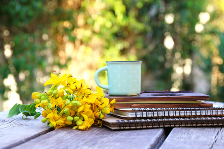 vintage objects: Image of notebooks next to field flowers on wooden table outdoors at afternoon. selective focus