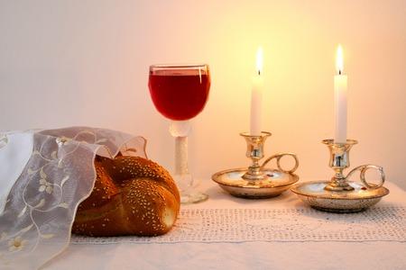 安息日のイメージ。カラのパン、安息日ワイン、木製のテーブルにカンデラ