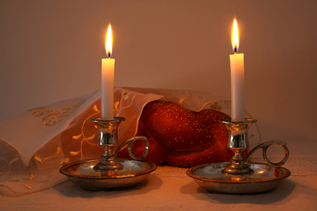 Low key shabbat image. challah bread, shabbat wine and candelas on wooden table Stock Photo
