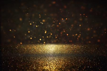 glittery: glitter vintage lights background. gold and black. de-focused.