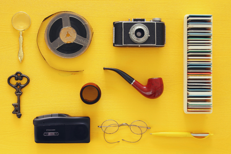 top view image of old camera, film and tape recorder over wooden yellow background. journalism or detective concept