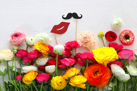 Top view of beautiful flowers arrangement, paper fake lips and mustache in sticks in front of white wooden background. Wedding, prom and engagement concept