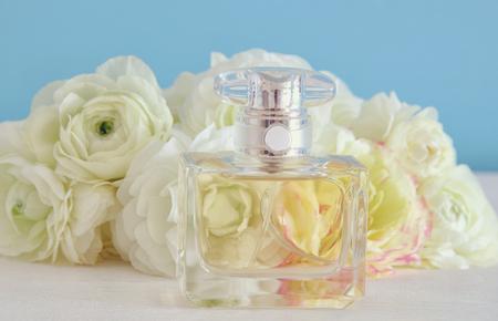 botella de perfume junto a las flores aromáticas en la mesa blanca.