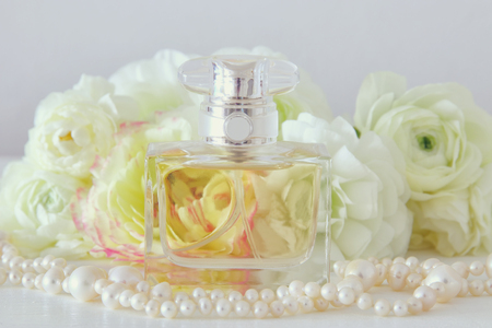 perfume bottle and pearls necklace next to aromatic flowers on white table