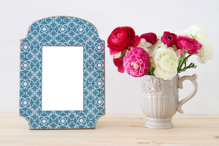 Image of beautiful bouquet of spring flowers next to blank vintage photo frame on wooden table. For photography mock up montage