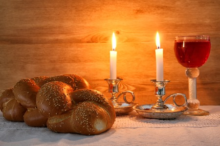 Low key shabbat image. challah bread, shabbat wine and candles on wooden table Zdjęcie Seryjne