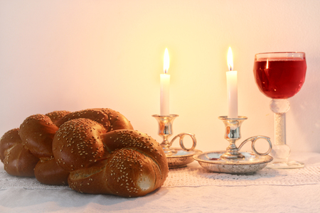 shabbat image. challah bread, shabbat wine and candles on wooden table