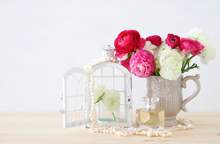 beautiful flowers: Beautiful bouquet of spring flowers in the vase next to pearls necklace and perfume bottle on wooden table Stock Photo