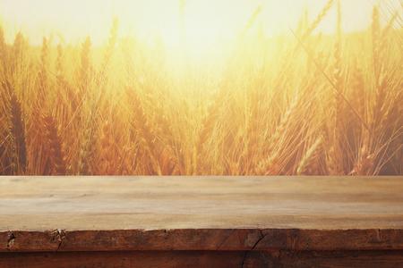 houten bord tafel voor gebied van tarwe op zonsondergang licht. Klaar voor montage van productweergave
