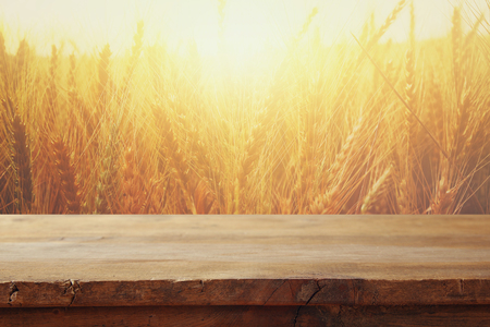 wood board table in front of field of wheat on sunset light. Ready for product display montage