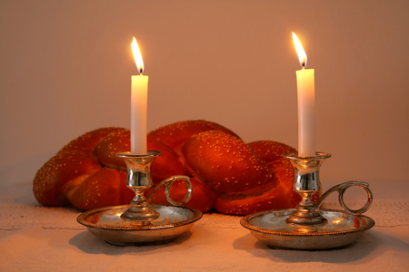 Low key shabbat image. challah bread, shabbat wine and candles on wooden table Stock Photo