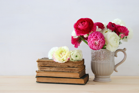 retro woman: Beautiful bouquet of spring flowers in the vase next to old books on wooden table Stock Photo