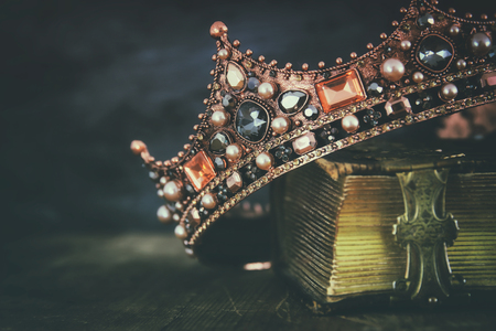 low key image of beautiful queen/king crown on old book. vintage filtered. fantasy medieval period Stockfoto