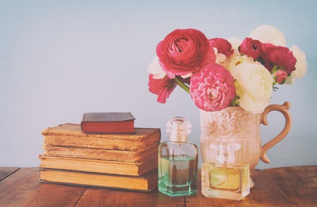 retro woman: Beautiful bouquet of spring flowers in the vase next to old books and perfume bottle on wooden table