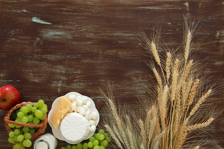 Top view image of dairy products and fruits on wooden background. Symbols of jewish holiday - Shavuot