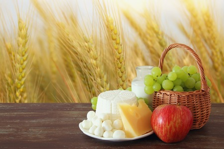 Image of dairy products and fruits on wooden table. Symbols of jewish holiday - Shavuot Imagens