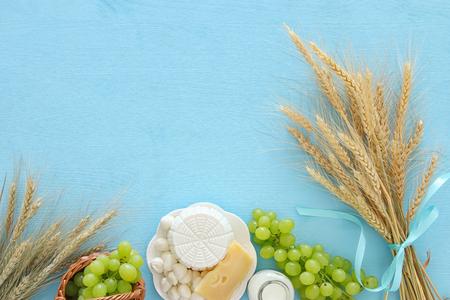 Draufsichtbild von Milchprodukten und von Früchten auf hölzernem Hintergrund. Symbole des jüdischen Feiertags - Shavuot