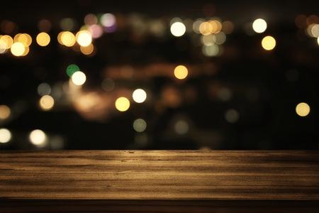抽象的なぼやけたレストランの前に木製のテーブルのイメージは、背景を点灯します。