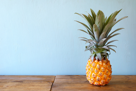 Pineapple on wooden table. Beach and tropical theme. Фото со стока