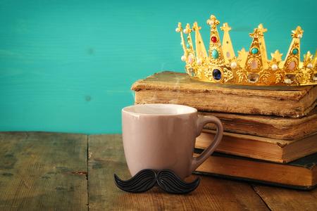 咖啡与髭和国王冠的在木桌上。父亲节概念