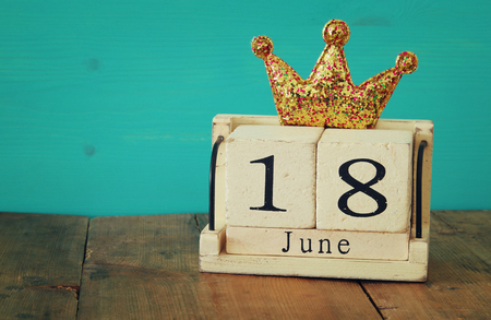 above 18: 18th of june. vintage calendar and glitter crown on old wooden table. Fathers day concept