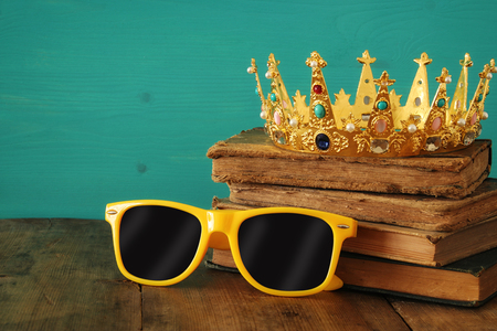 Individuality and unique concept. Old medieval gold crown and cool sunglasses on wooden table Stock Photo