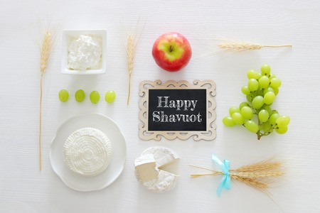Top view image of dairy products and fruits on white wooden background. Symbols of jewish holiday - Shavuot
