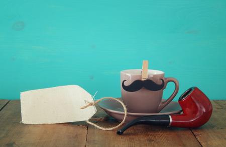 咖啡与小胡子和抽烟管子的在木桌上。父亲节概念