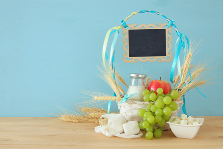 image of dairy products and fruits on wooden table. Symbols of jewish holiday - Shavuot