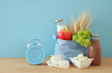Healthy breakfast next to alarm clock waking up at morning on wooden table