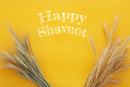top view of wheat crop on wooden table. Symbols of jewish holiday - Shavuot