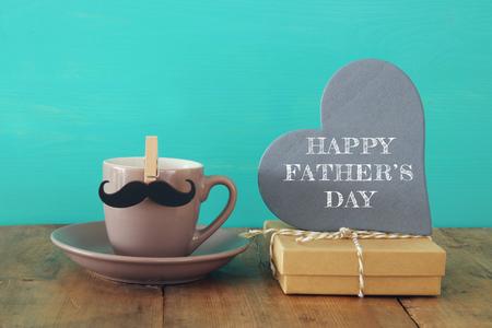 礼品盒旁边放着一杯带胡子的咖啡,桌子上放着一颗木制的心。父亲节概念