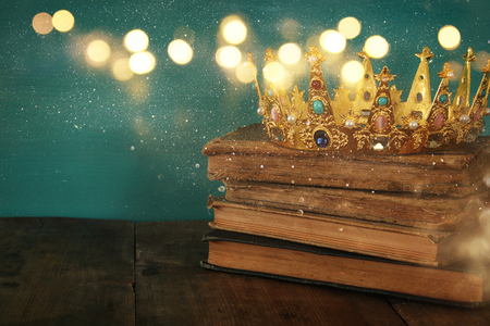 photo story: low key image of beautiful queenking crown on old book. vintage filtered. fantasy medieval period. Glitter overlay