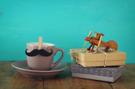 给爸爸的礼物旁边的桌子上放着一杯咖啡和小胡子。父亲节概念