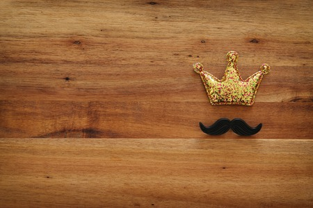 Top view image of funny mustache and glitter crown on wooden background. Fathers day concept