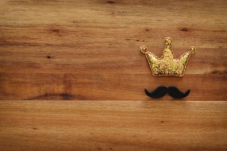 俯视图图像滑稽的胡子和闪闪发光的皇冠在木制的背景。父亲节的概念