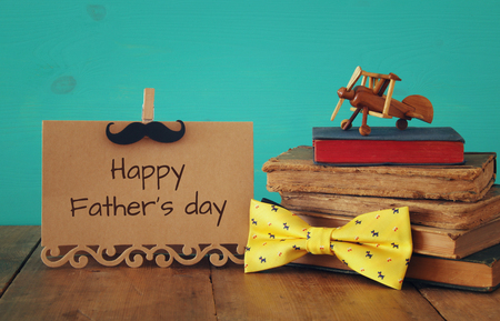 funny mustache, greeting card, bow and books on wooden table. Father's day concept
