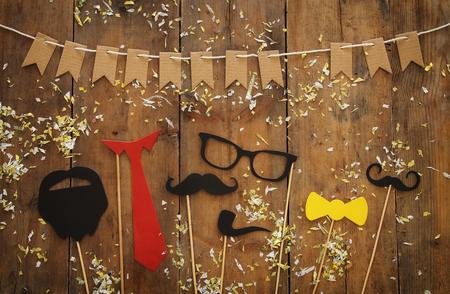 面白いひげ、眼鏡、口ひげ、ネクタイ、木製の背景に弓の平面図イメージ。父の日の概念
