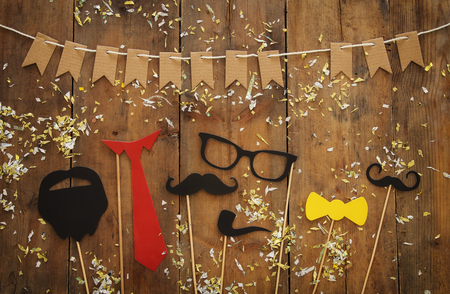 Top view image of funny beard, glasses, mustache, tie and bow on wooden background. Fathers day concept