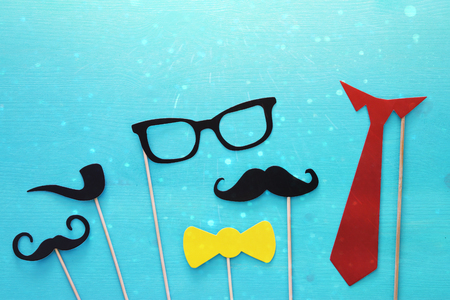 Top view image of funny beard, glasses, mustache, tie and bow on wooden background. Father's day concept. Glitter overlay