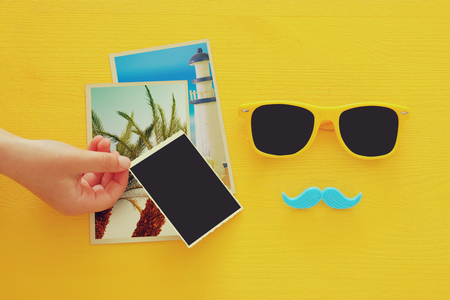 photo album: Fathers day concept. Hipster yellow sunglasses and funny moustache next to blank photographs on yellow background. For photographs montage