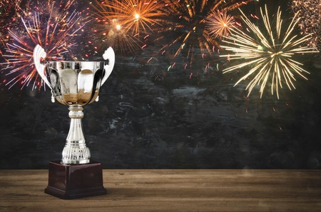 champ: low key image of trophy over wooden table and dark background, with abstract fireworks Stock Photo