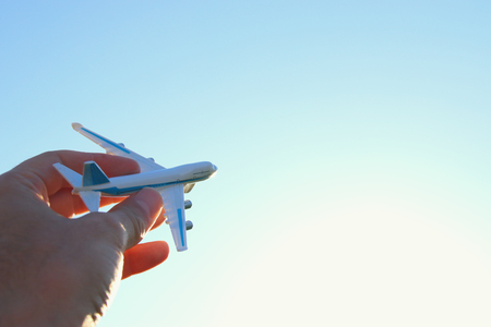 close up photo of mans hand holding toy airplane against blue sky Stock fotó