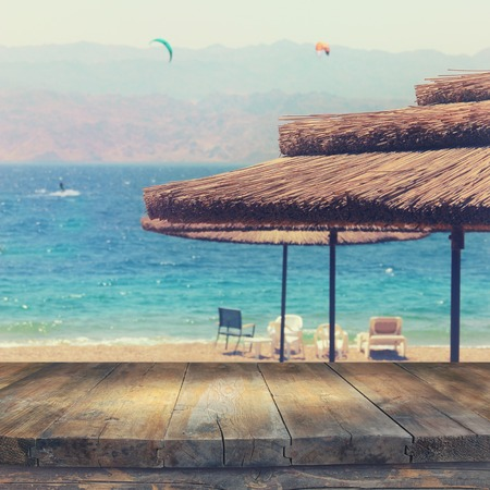 Empty old table in front of tropical sea and beach. Summer travel and vacation concept. Useful for product display montage. Vintage filtered