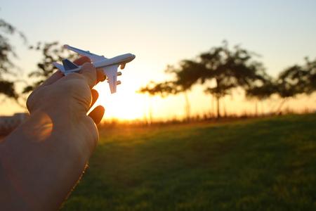 Vicino fotografia della mano dell'uomo che tiene aeroplano del giocattolo contro il cielo di tramonto Archivio Fotografico - 80921316