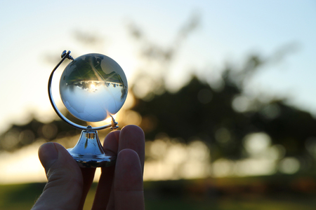 男性の手の日没の前に小さなクリスタル ☆ 地球儀。旅行や地球規模の問題の概念