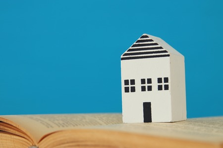 small house model over open book. selective focus.
