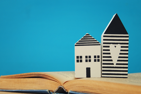 lodgings: small house model over open book. selective focus.